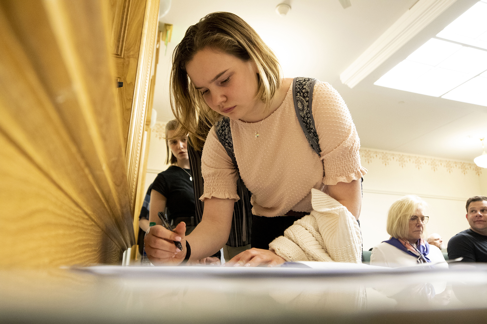 Meagan Figgins, an 11th grader from Nederland High School, signs up to testify before the state's Health and Insurance Committee on March 4, 2020. (Kevin J. Beaty/Denverite)