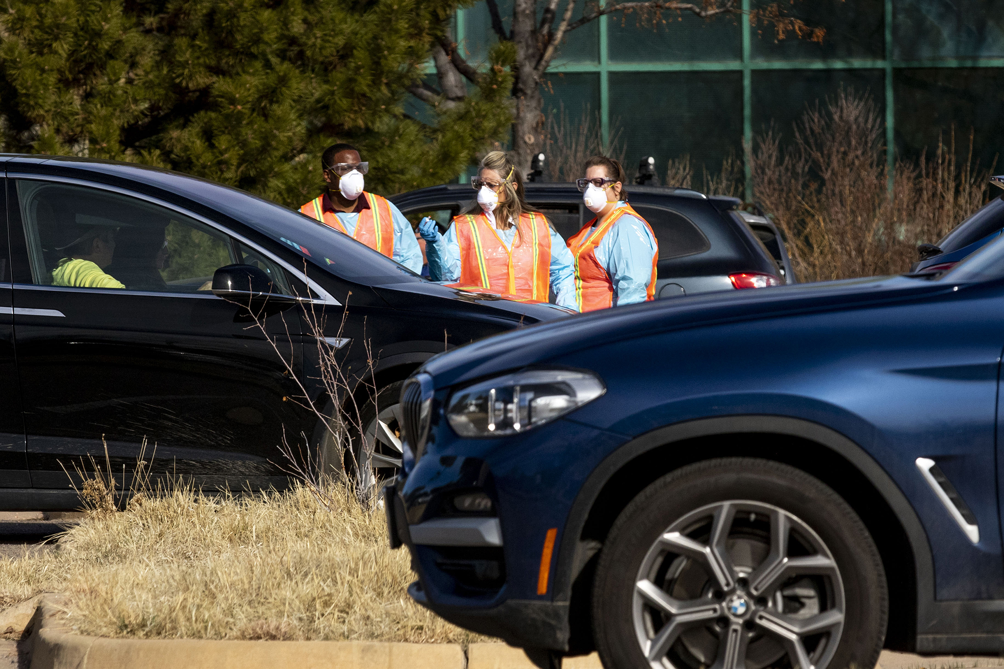 Workers survey people in cars waiting to be tested at the Colorado Department of Health and Environment's COVID-19 testing station in Lowry. March 11, 2020. (Kevin J. Beaty/Denverite)