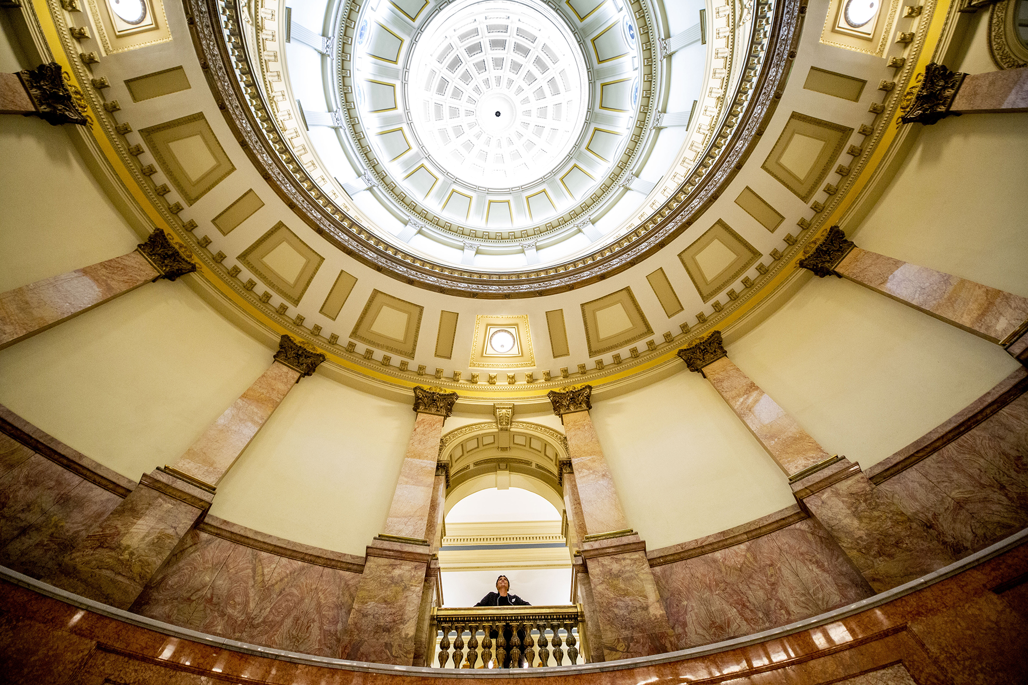 A woman peers into the Colorado State Captiol rotunda. March 12, 2020.