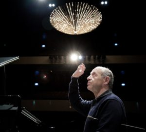 Maestro Iván Fischer looks up with his hand raised to conduct