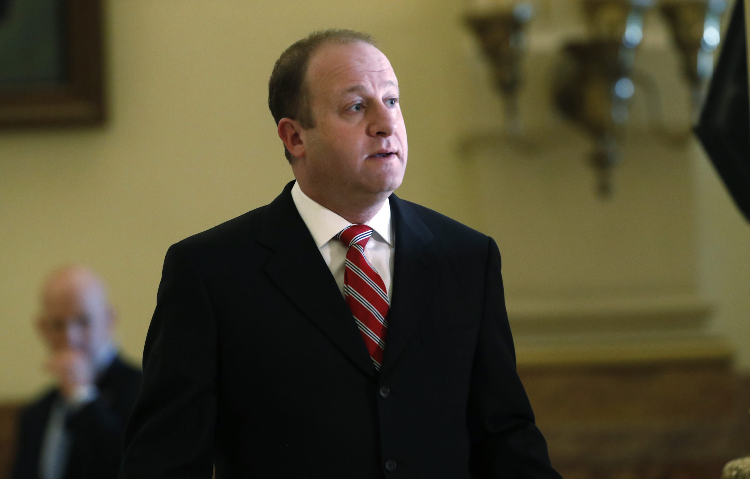 Colorado Gov. Jared Polis heads to the podium to address a news conference about the state's efforts to fend off the spread of coronavirus Monday, March 16, 2020, in Denver.