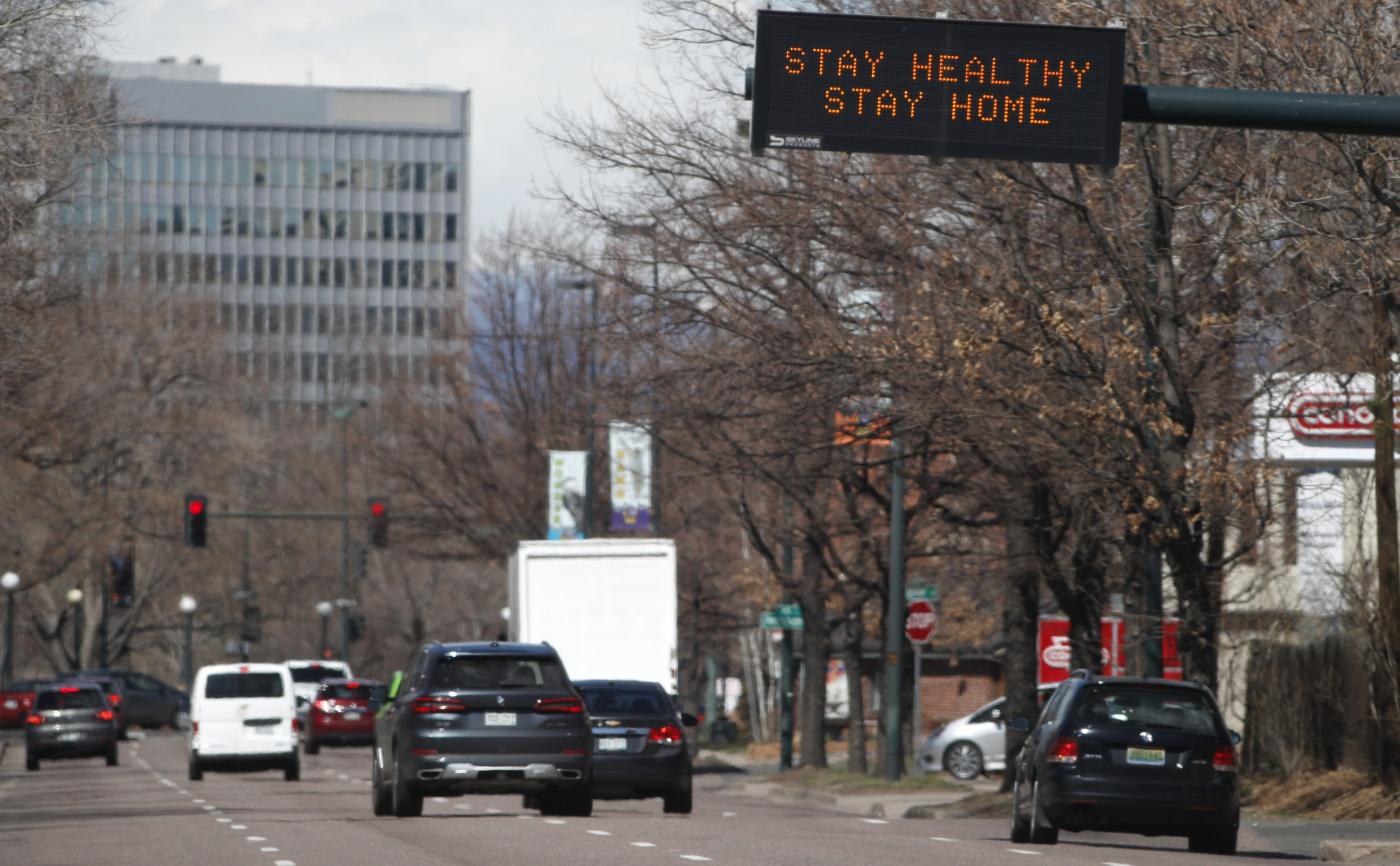 """A traffic sign over westbound Speer Boulevard tells motorists to stay home as a mayoral """"stay at home"""" edict goes into effect until Friday, April 10, in an effort to reduce the spread of the new coronavirus Tuesday, March 24, 2020, in Denver."""