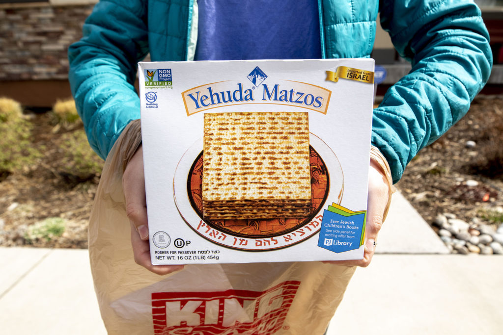 Sadie Ladis holds up some Yehuda Matzos for Passover that she's delivering to a fellow member of Temple Micah, who can't leave the house during the COVID-19 outbreak on April 3, 2020.