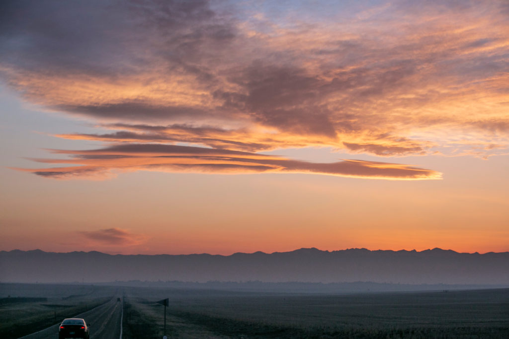 A car speeds westward in rural Adams County as the sun sets behind the Rocky Mountains