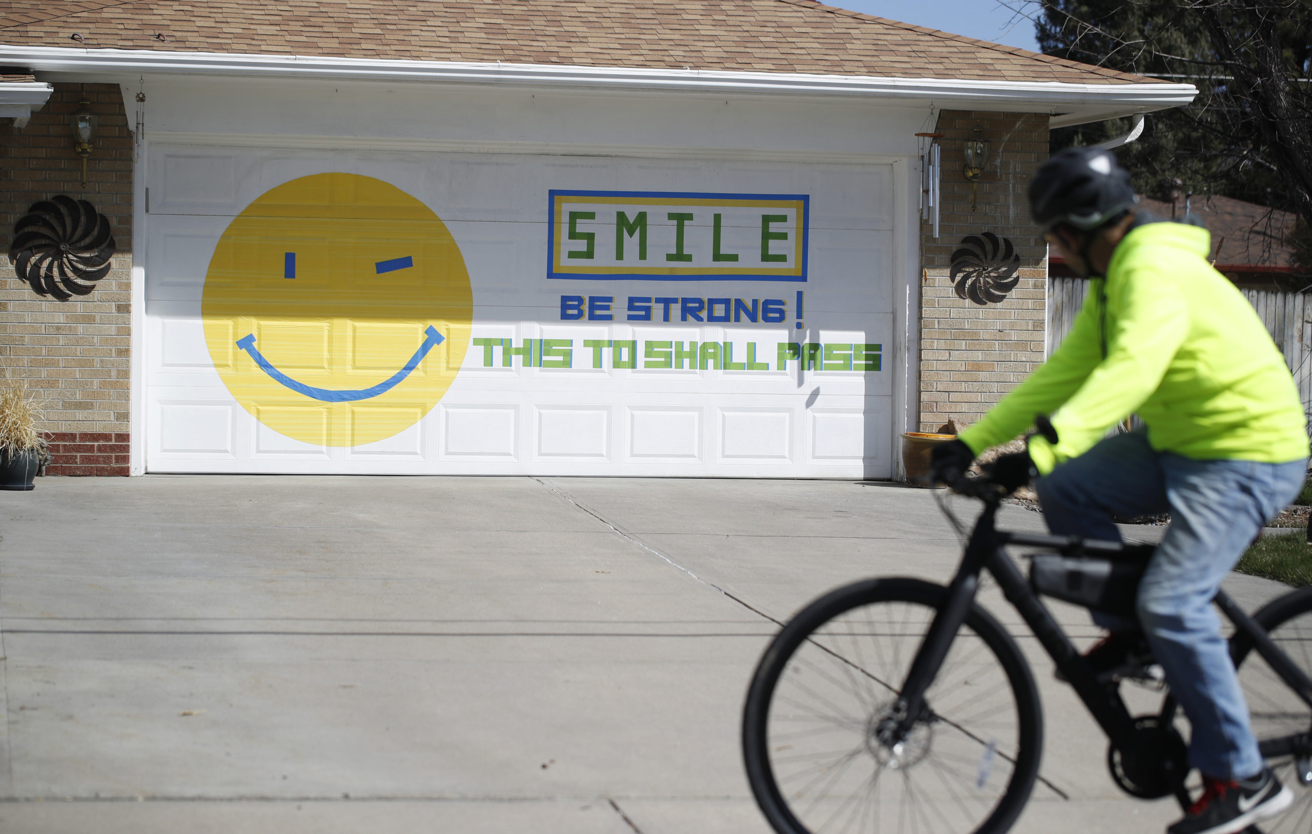 A bicyclist looks at the message on the garage door of a home on Grandview Avenue as a statewide stay-at-home order remains in effect in an effort to reduce the spread of the new coronavirus Tuesday, March 31, 2020, in Arvada, Colo.