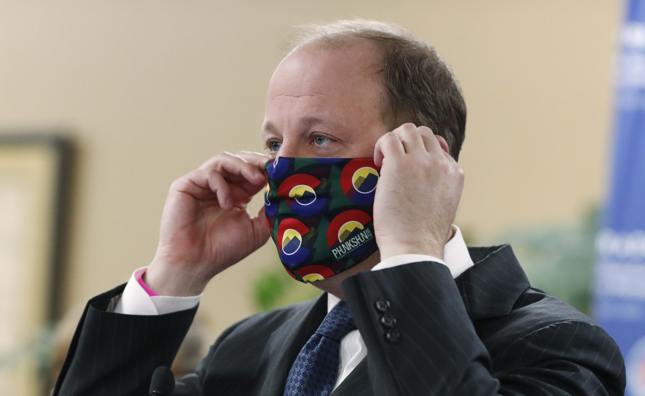 Colorado Governor Jared Polis dons a mask to encourage state residents to wear them while in public as a statewide stay-at-home order remains in effect in an effort to reduce the spread of the new coronavirus Friday, April 3, 2020, in Centennial, Colo.