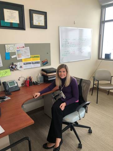A picture of Andrea Rehmert at her desk in the VA.