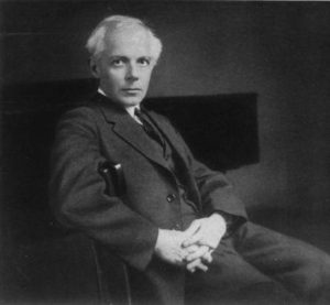 Black and white photograph of Bela Bartok seated with his hands clasped in front of him.