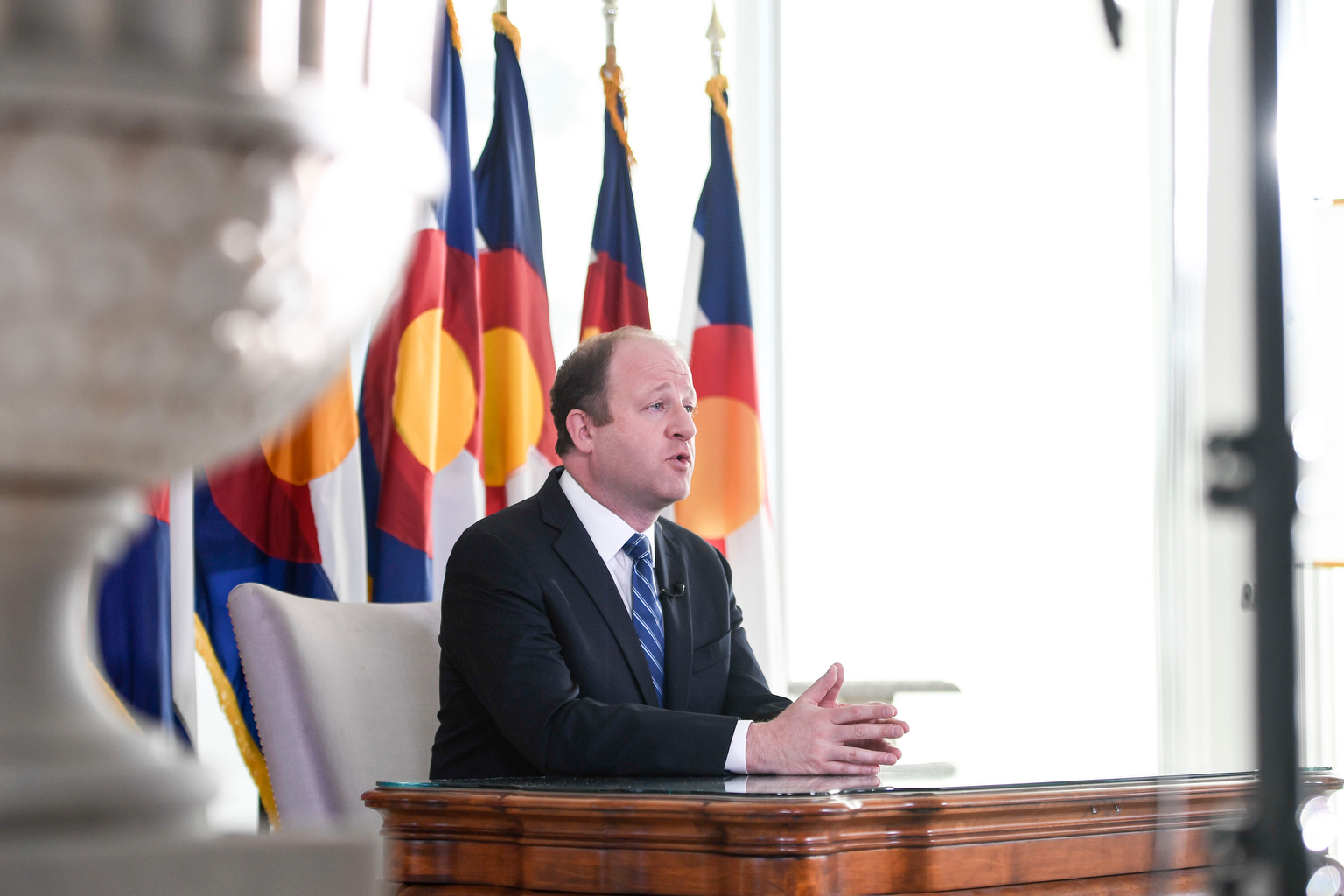 Jared Polis delivers an address from the governor's mansion on Monday, April 6