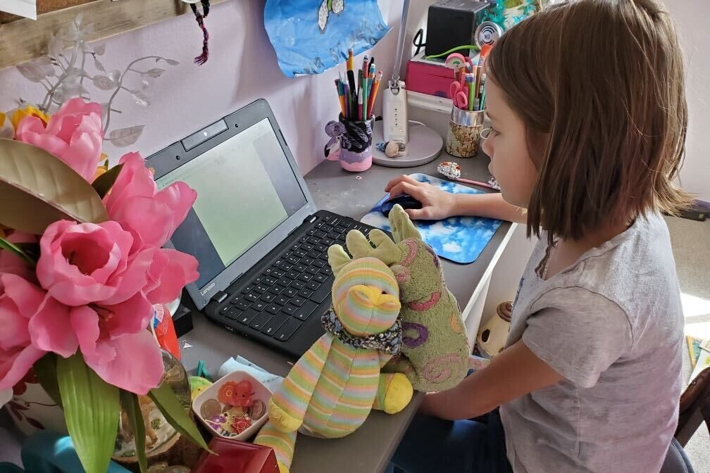 Nine-year-old Evy does homework on her laptop as schools close due to the coronavirus pandemic.