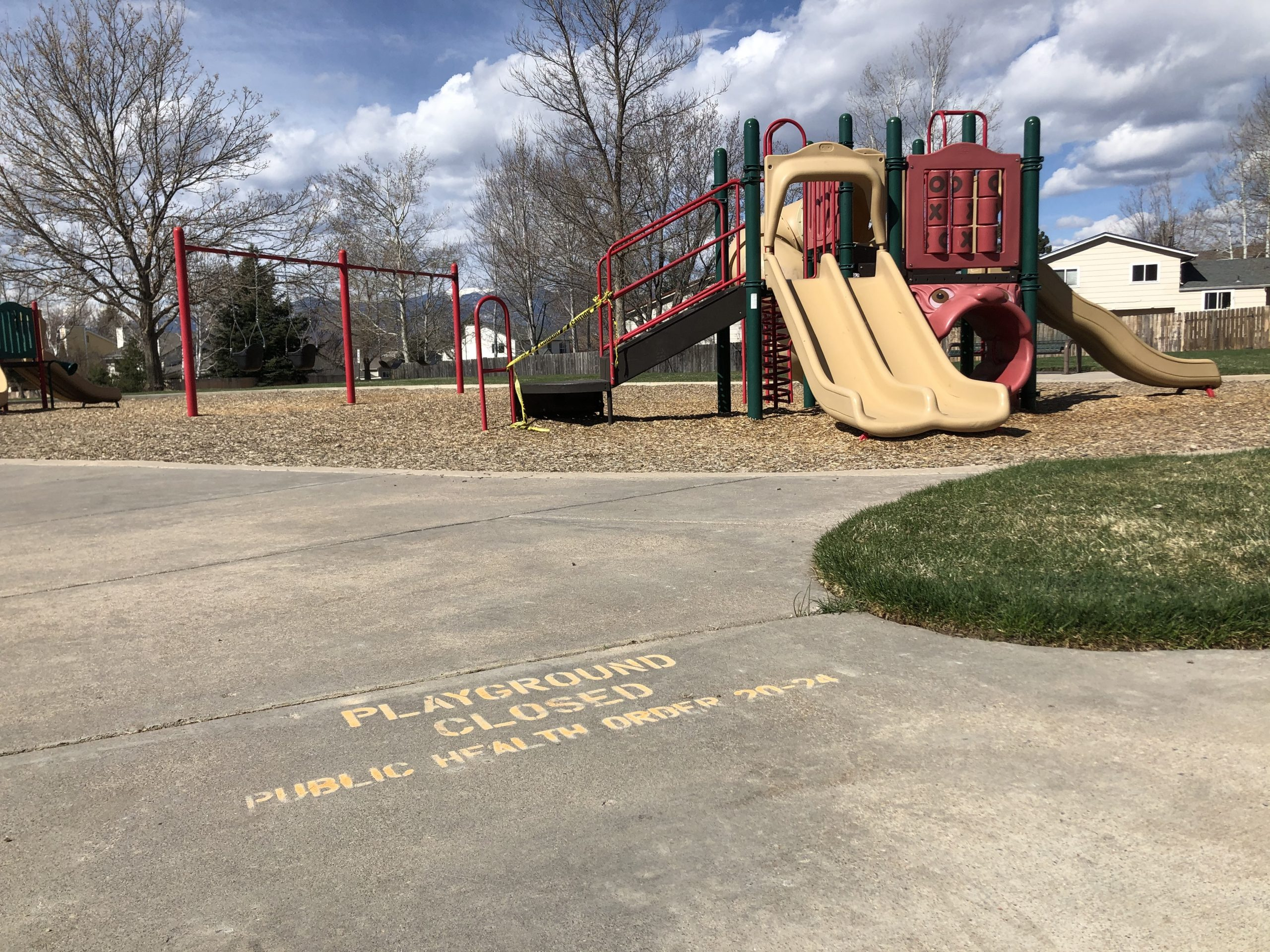A playground in Colorado Springs indicates with writing on the pavement and tape around the equipment that it's closed due to public health orders.
