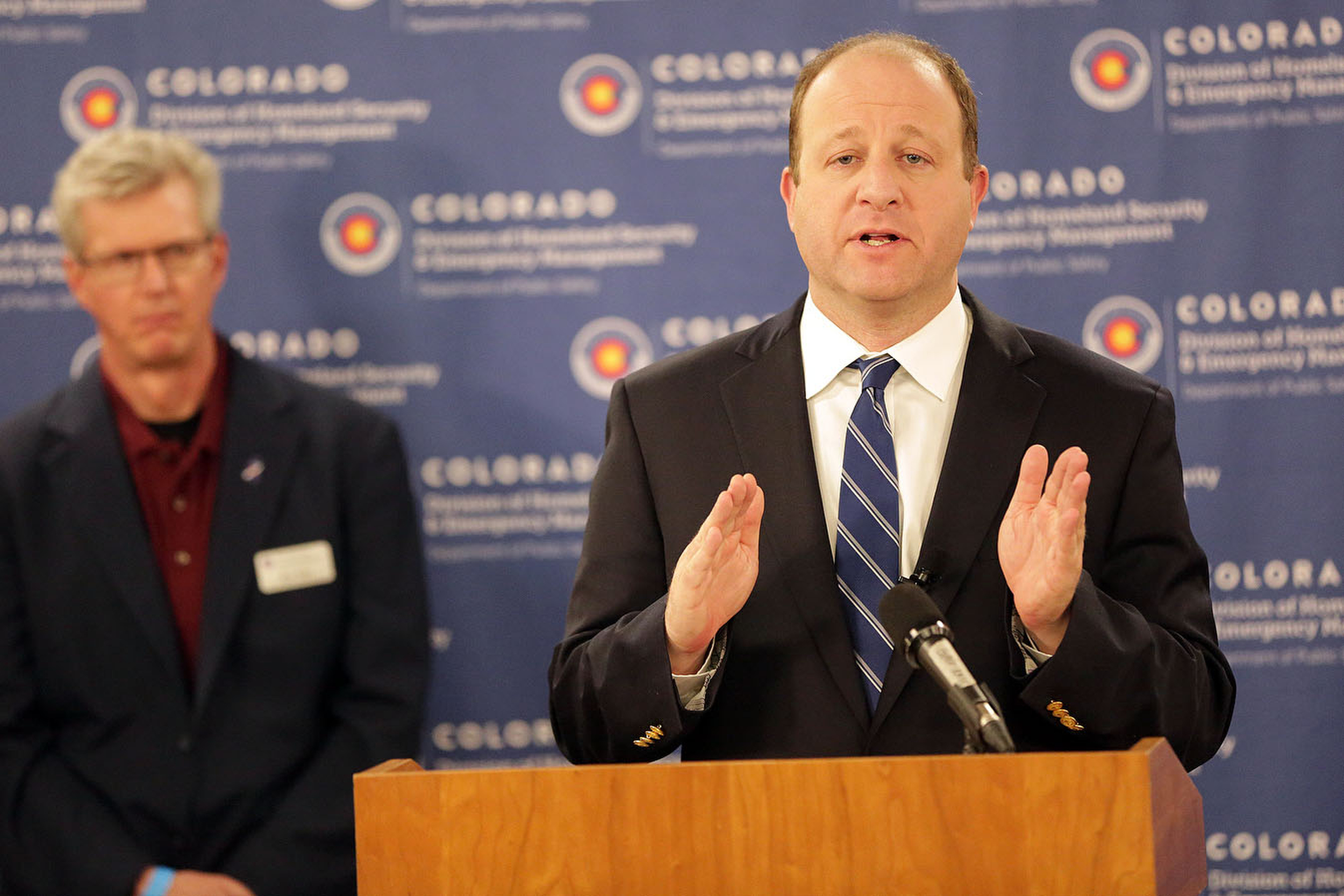 Colorado Gov. Jared Polis gestures during a press conference on March 25