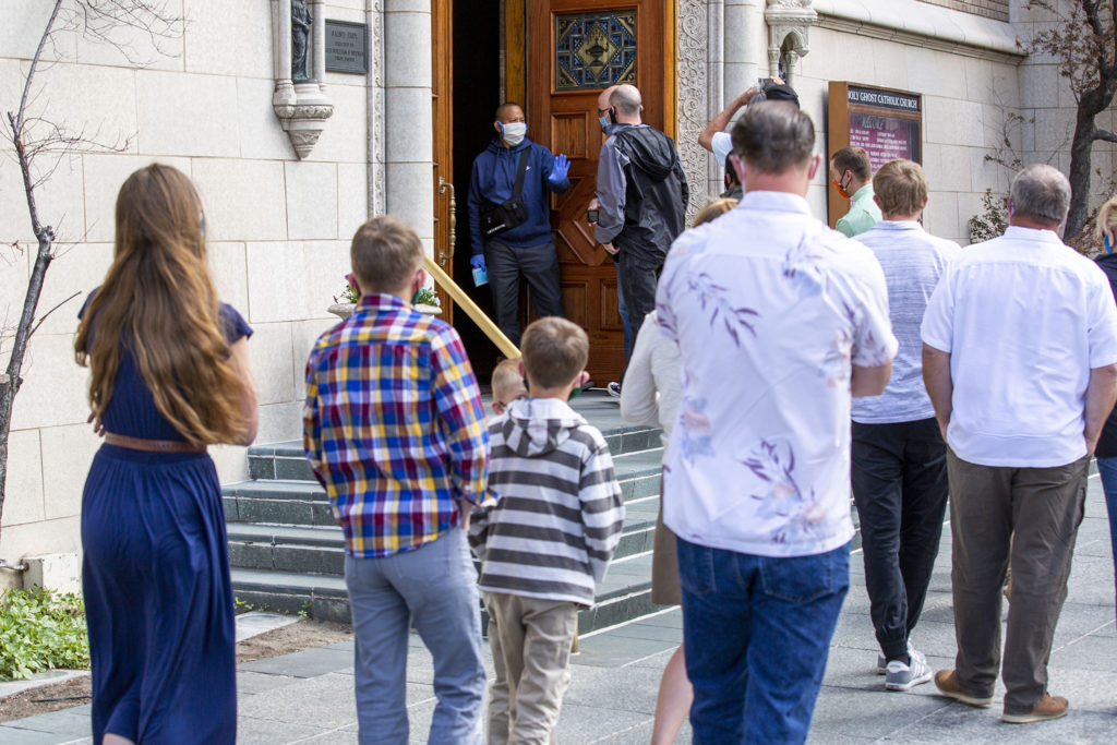 Parishoners wait to enter Holy Ghost Catholic Church in small, socially distant groups. May 9, 2020.
