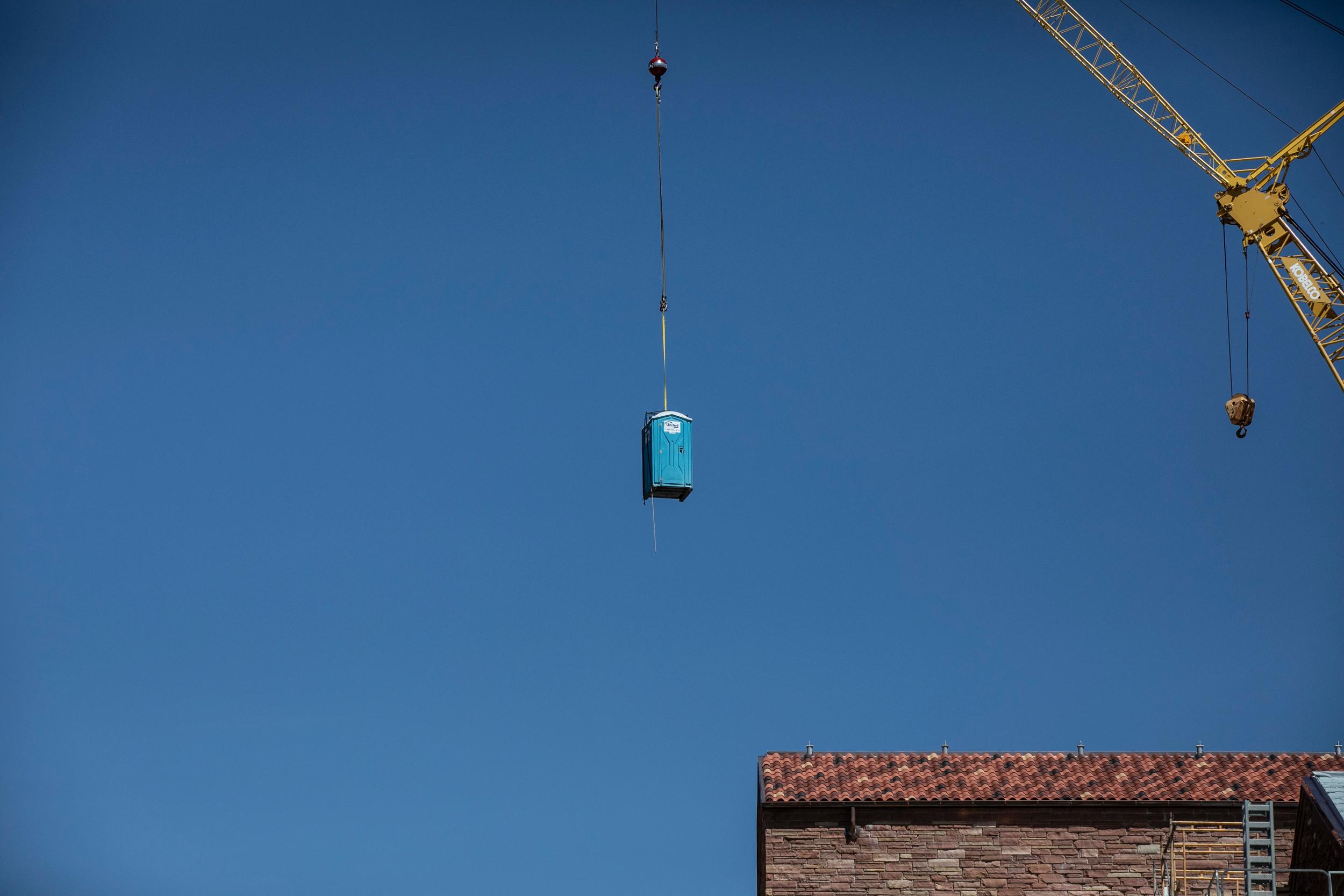 Crane lifts a portable toilet over a construction site at the University go Colorado at Boulder
