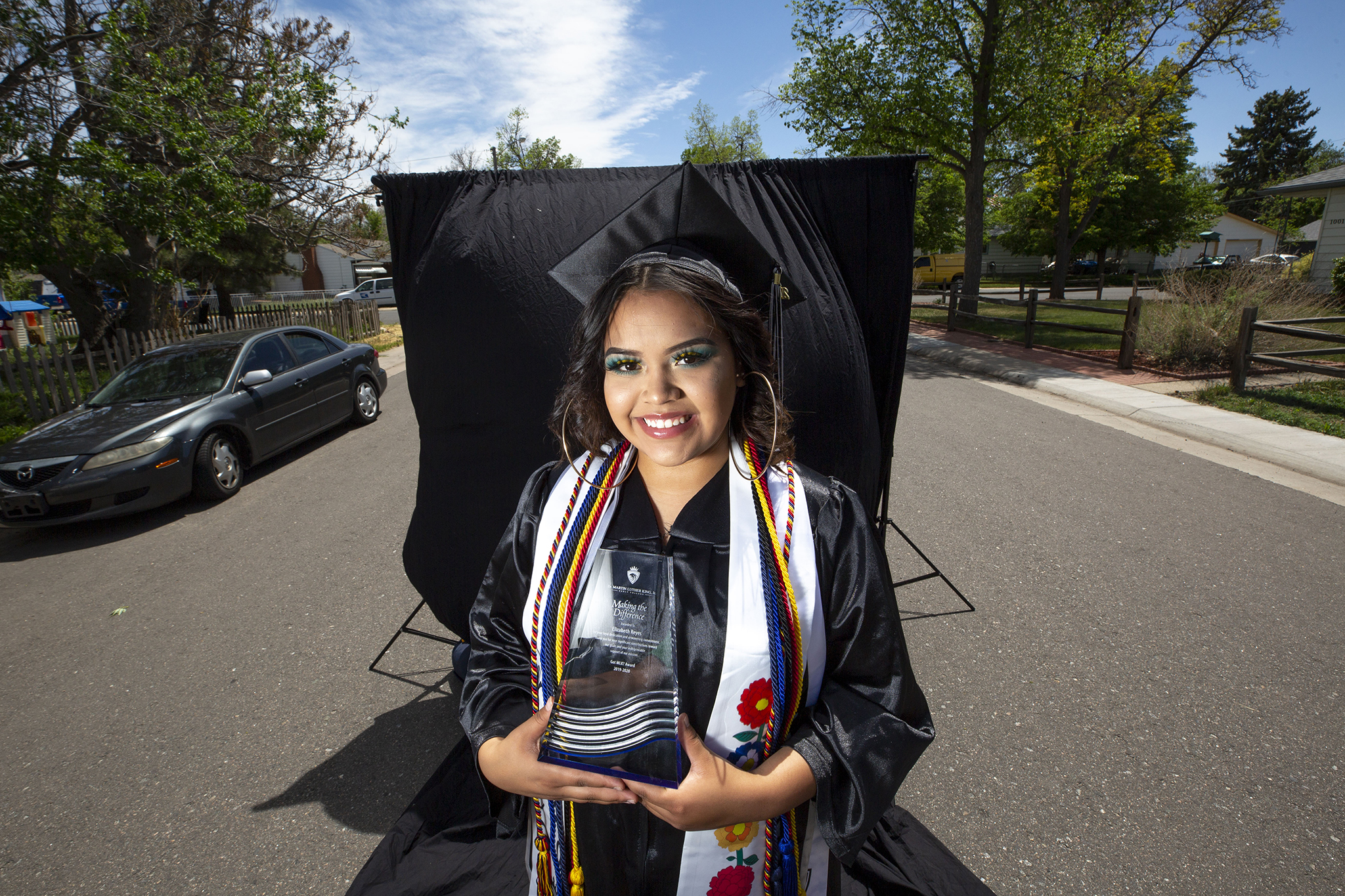 MLK Jr. Early College graduate Elizabeth Reyes poses for a cap-and-gown portrait in front of the house where she's been living in Aurora on May 20, 2020.