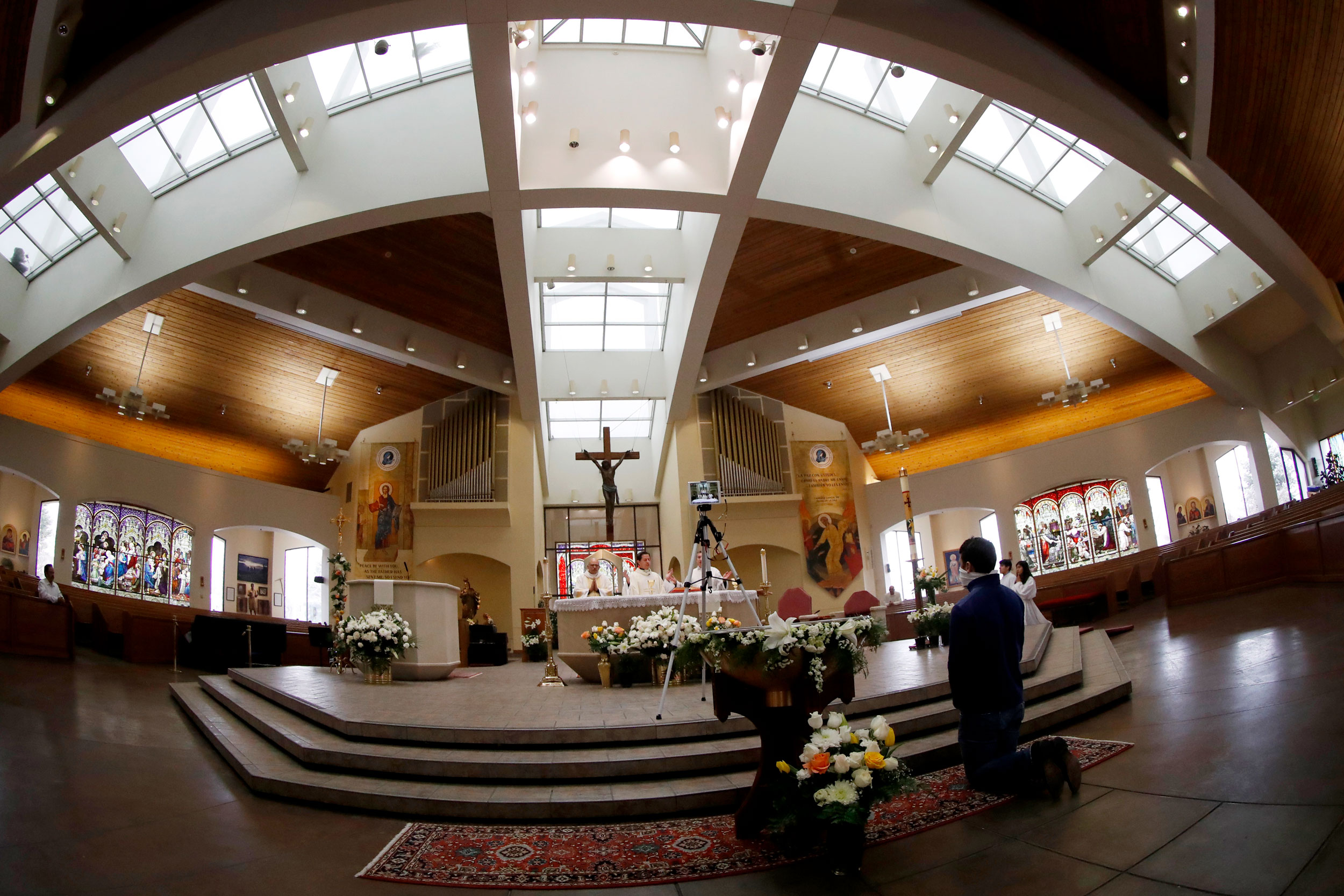 From left, Deacon Efra Pruneda, Father Jesus Murillo and Father Felix Medina deliver Easter Mass in Spanish during a broadcast of services because of the new coronavirus Sunday, April 12, 2020, in Queen of Peace Catholic Church in Aurora, Colo.