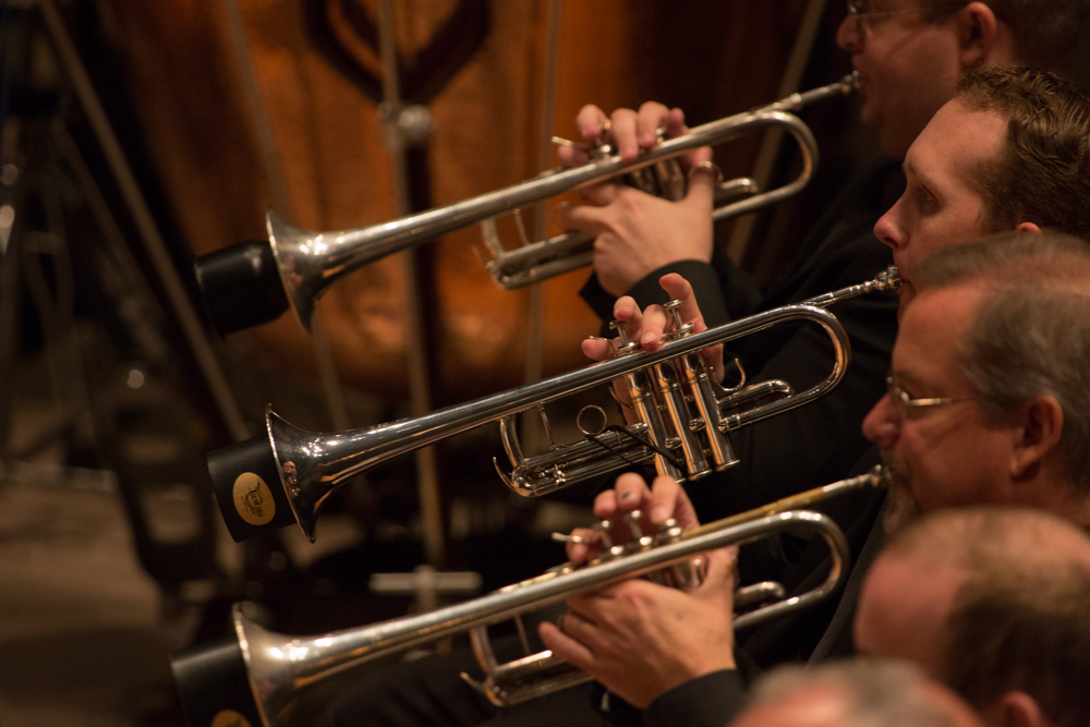 3 trumpet players in profile in the midst of the Colorado Symphony Orchestra