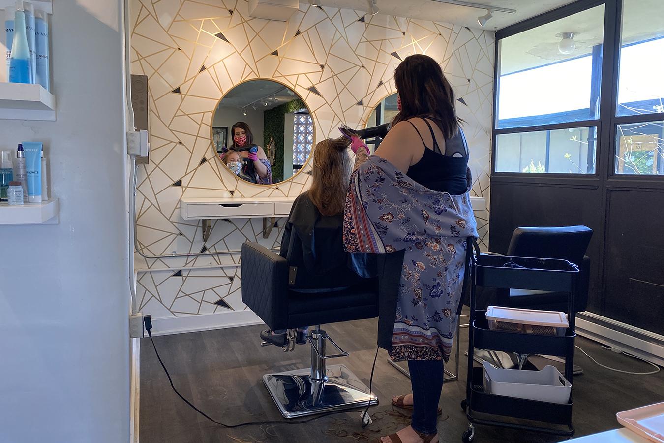 Blush Beauty Bar hair salon owner Mindy Bodley cuts Amy Eldridge's hair on May 5 in Loveland, Colorado. Eldridge was the salon's first customer following a seven-week shutdown due to COVID-19 stay-at-home orders.