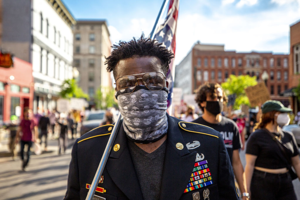 Aubrey Rose, an 18-year U.S. Army veteran, marches with an upside-down American flag over his shoulder. A march reacting to the death of George Floyd comes face to face with authorities at 20th Street and Chestnut Place. May 28, 2020.