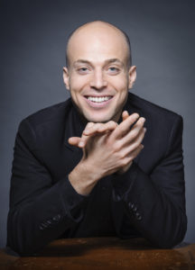 Pianist Orion Weiss smiles at the camera with his hand under his chin