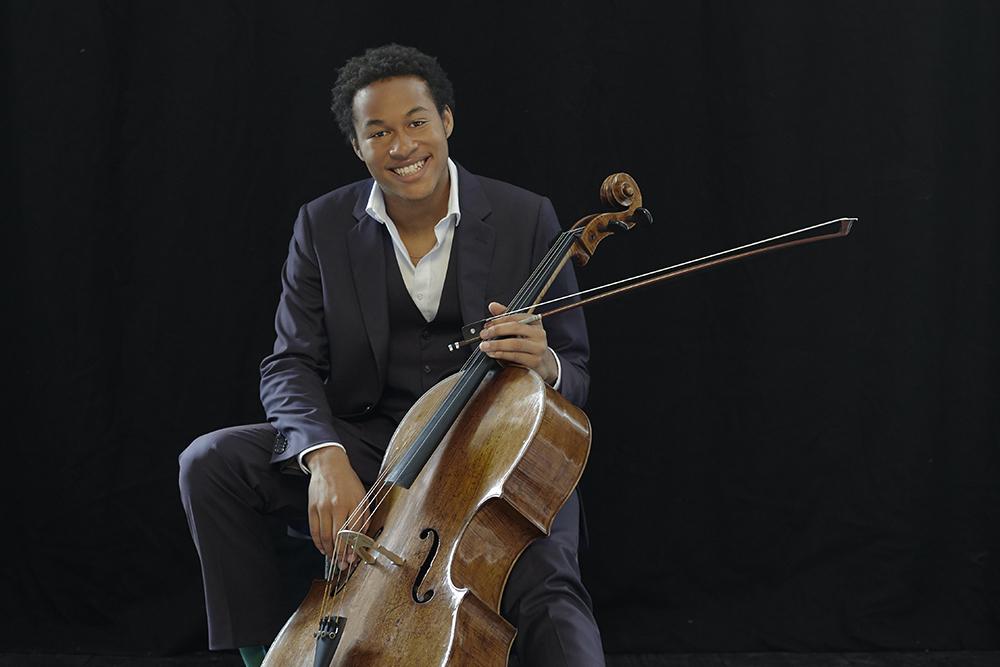 Sheku Kanneh-Mason sits holding his cello, smiling at the camera