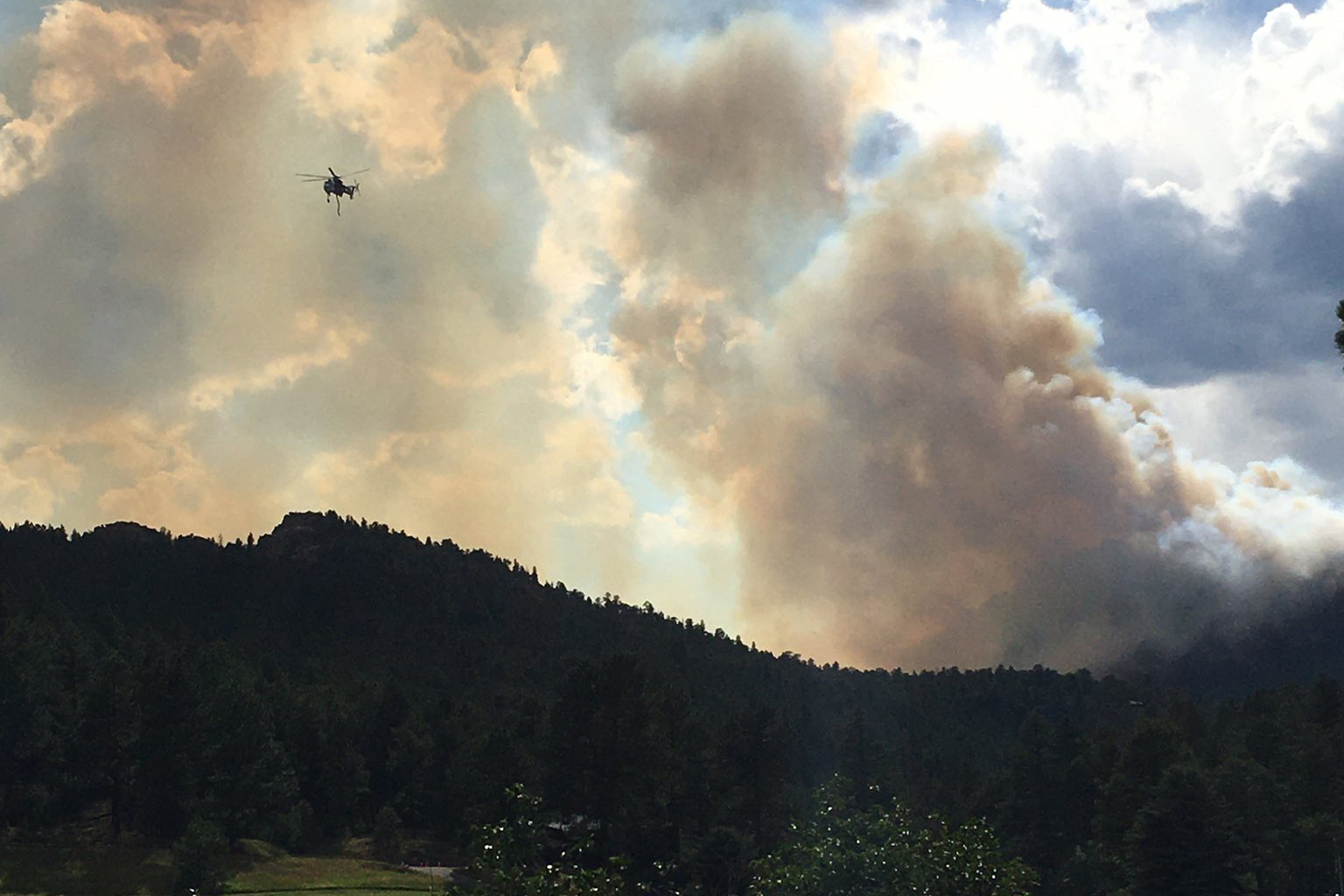 A helicopter flies by the Elephant Butte Fire near Evergreen on Monday, July 13.