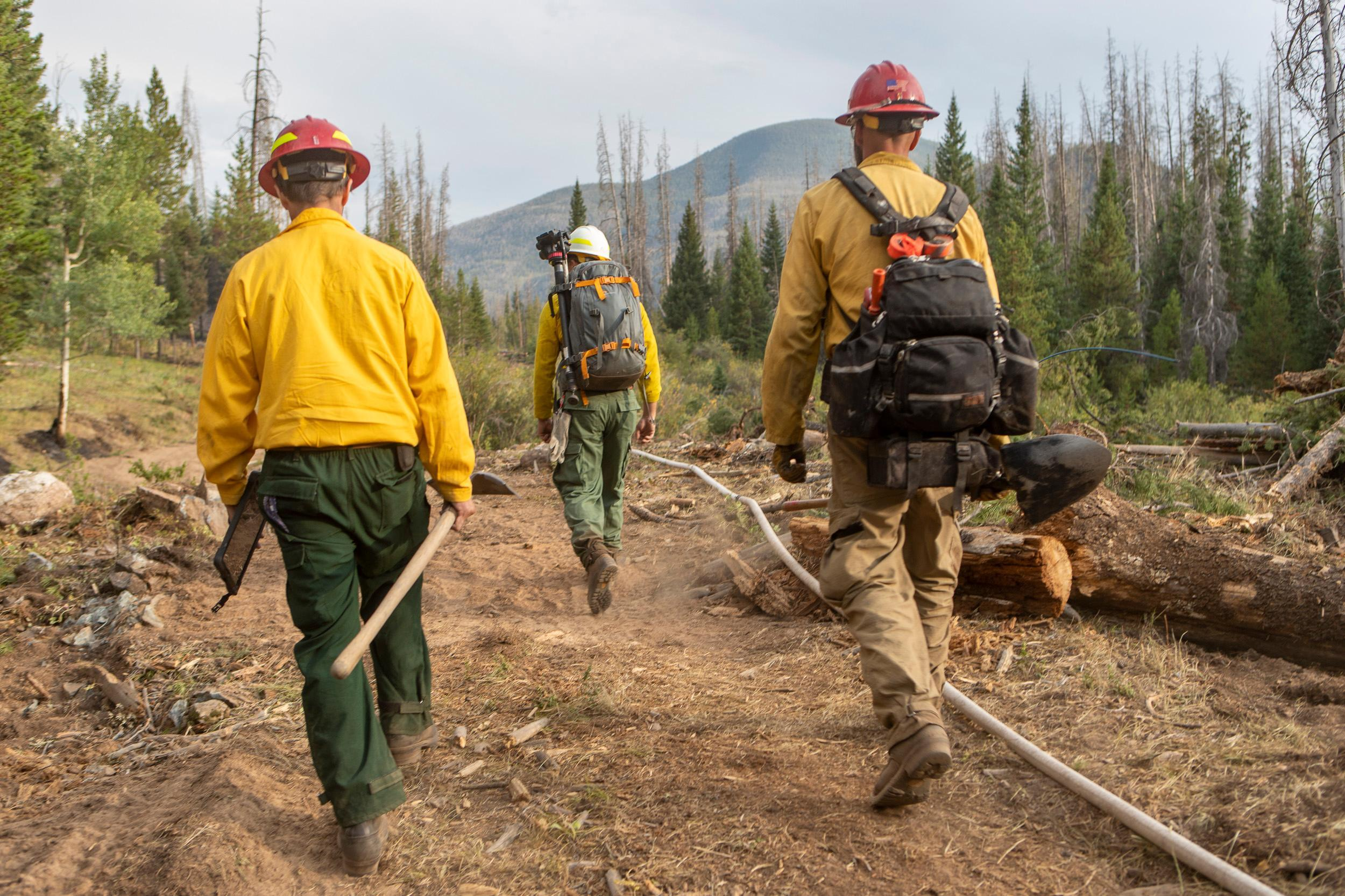 Chuck Rhodes, Research Biogeochemist with the Rocky Mountain Research Station hikes containment line with Task Force Leader Erik Bloom during an educational video shoot with Videographer Aaron Colussi, center front, at the Williams Fork Fire.