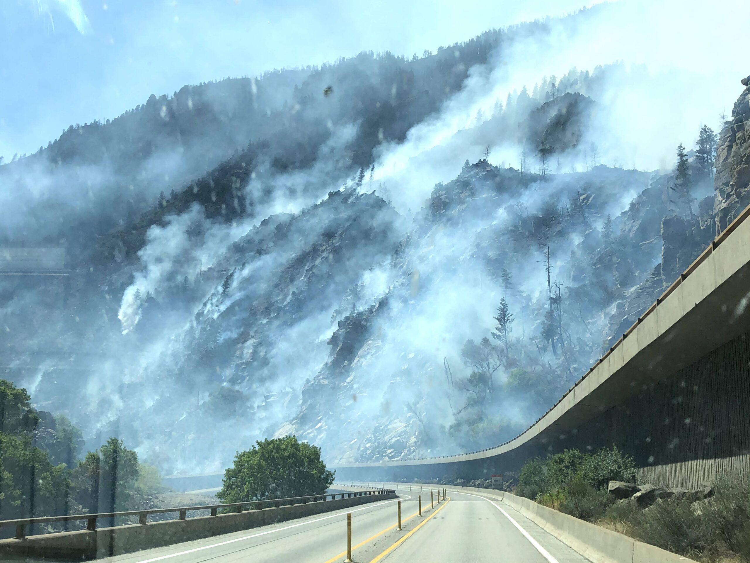 Smoke rises from the walls of Glenwood Canyon, where the Grizzly Creek fire has kept I-70 closed for days.