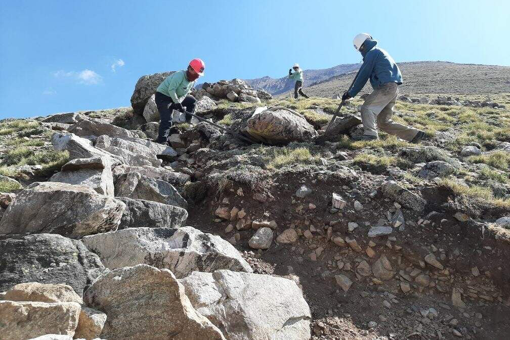 Colorado Fourteeners Initiative crews work to move large boulders and rocks as they create a hiking trail on Colorado's Mt. Columbia near Buena Vista.