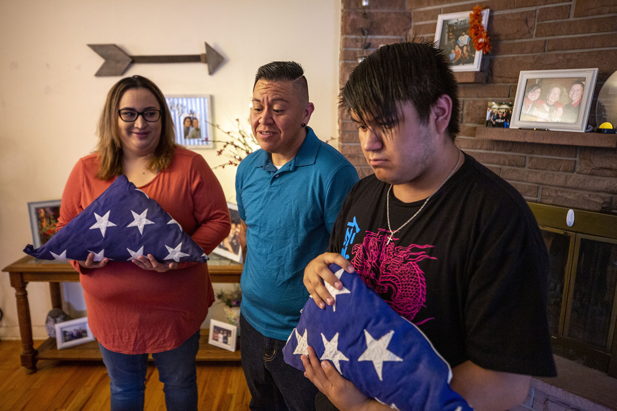 Vanessa (left to right), Kris and Jacob Garcia hold military flags that belonged to Kris' father, Alfredo, in their home in Denver's College View - South Platte neighborhood. Sept. 20, 2020.