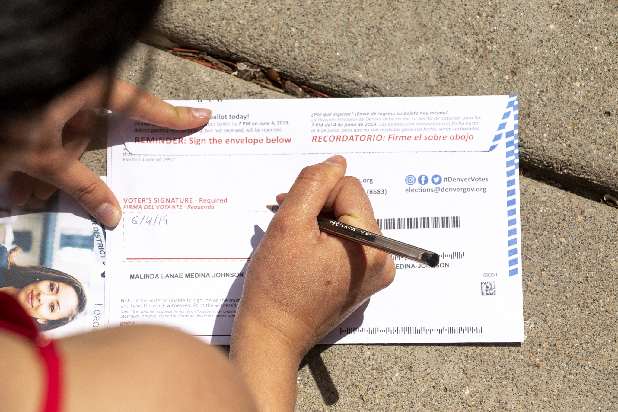 A voter fills out her ballot outside of her home in Denver's Five Points neighborhood, June 4, 2019.