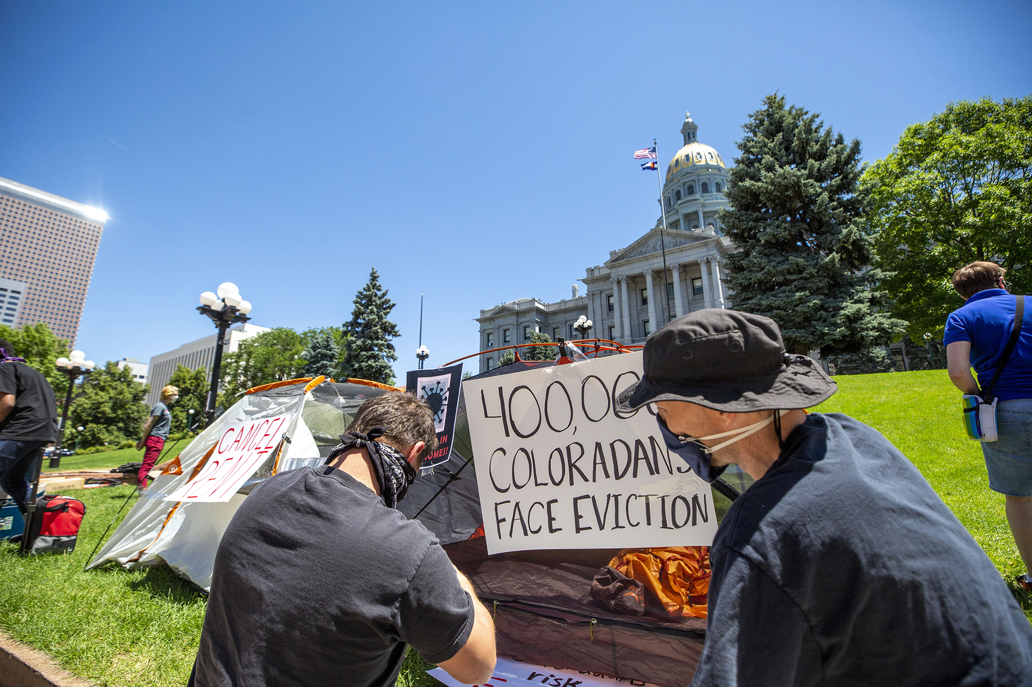Kevin Breidenbach and Luke Wierman post signs to tents as the Denver Democratic Socialists of America protest rent and evictions as the economy continues to struggle during the pandemic. July 1, 2020.