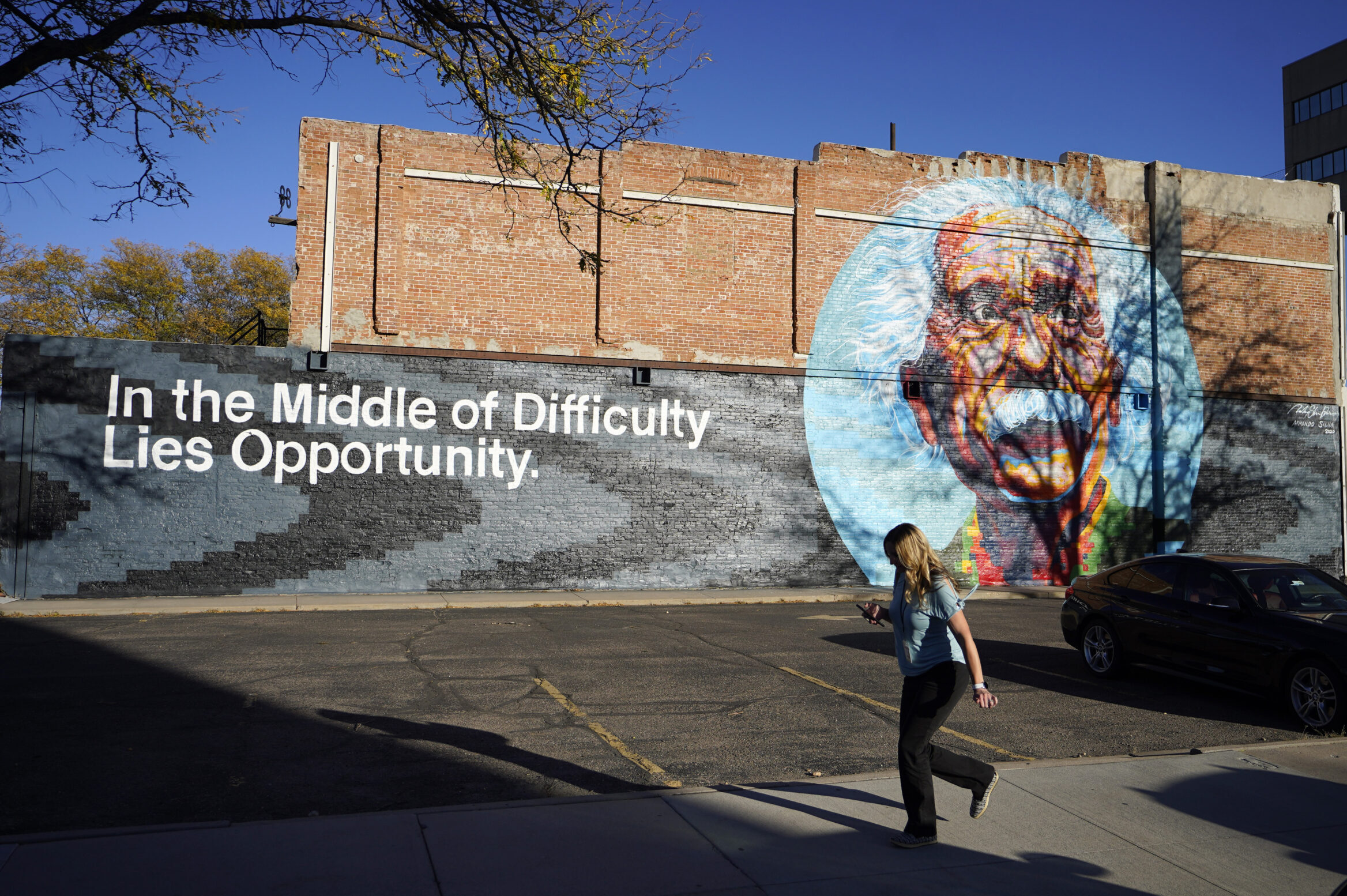 A pedestrian moves past a mural of Albert Einstein in Greeley.