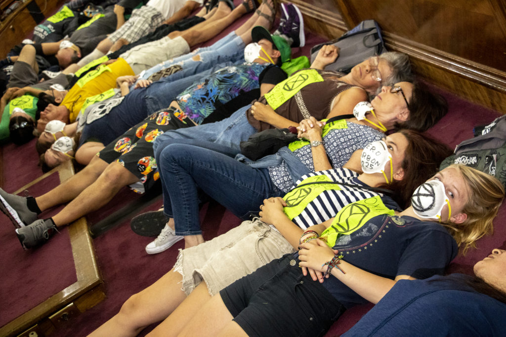 "Climate change activists perform a ""die-in"" during Denver City Council. Aug. 5, 2019. (Kevin J. Beaty/Denverite)"