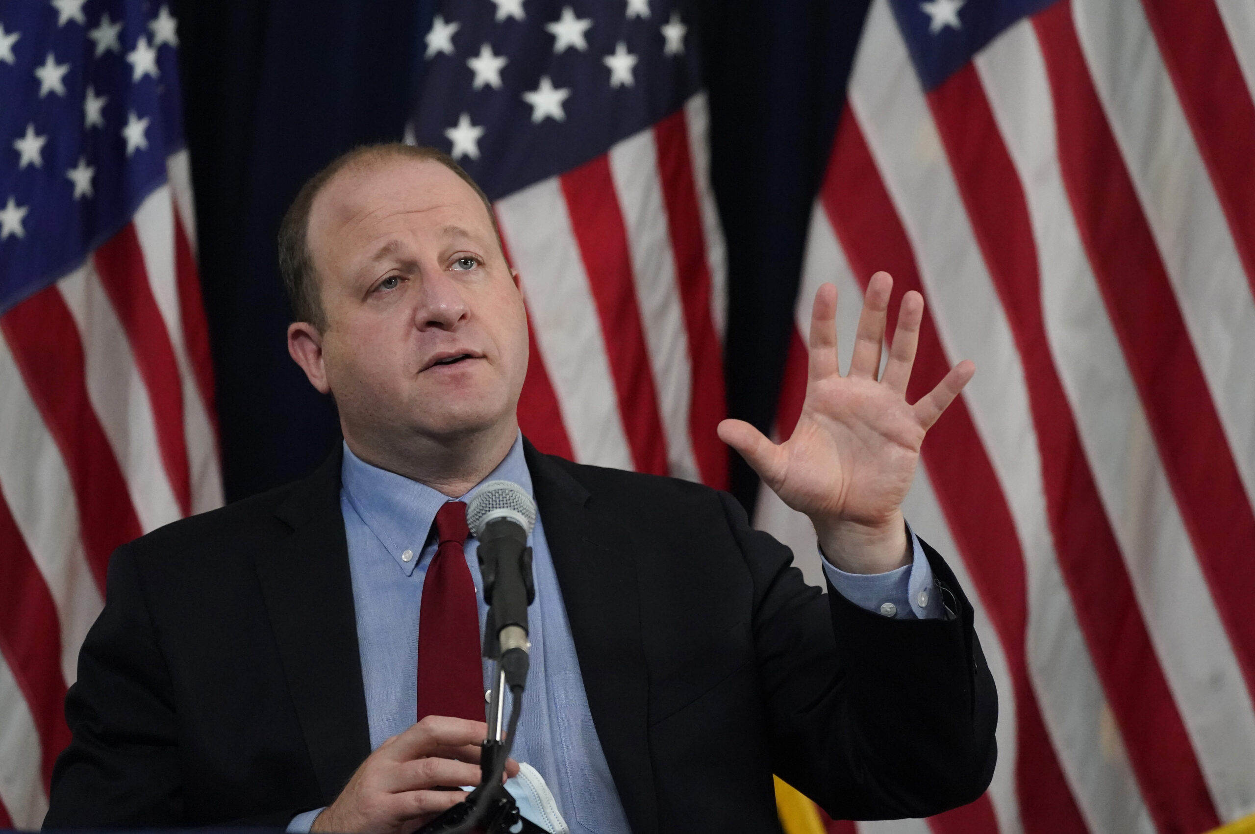 Colorado Gov. Jared Polis makes a point during a news conference Tuesday, Oct. 13, 2020, in Denver.