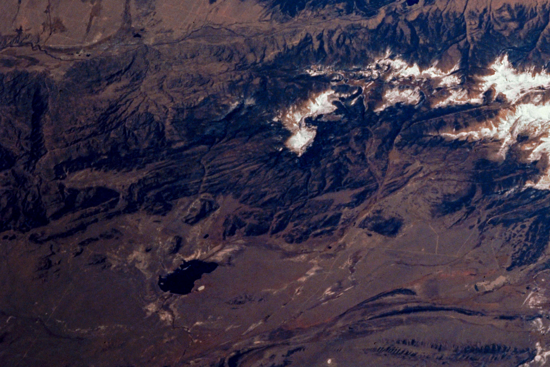 Antero Reservoir as seen from space and photographed during STS-58 in October of 1993. The reservoir appears as a dark blotch near the lower left of the photograph.