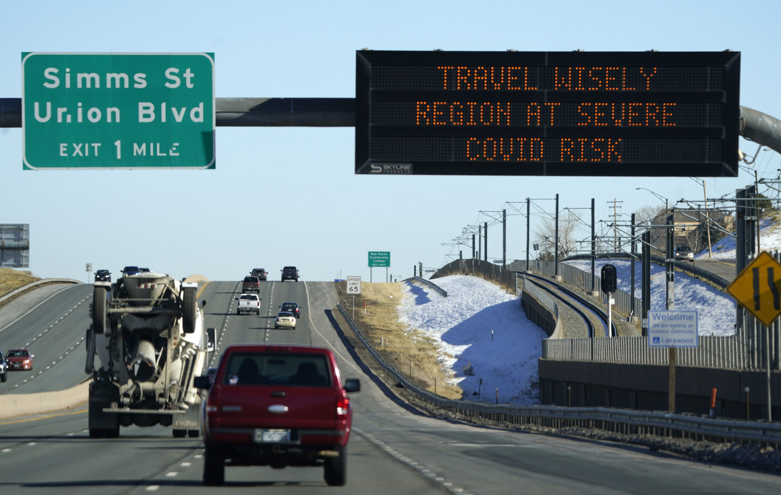 Highway sign warns of high COVID-19 risk in Colorado.