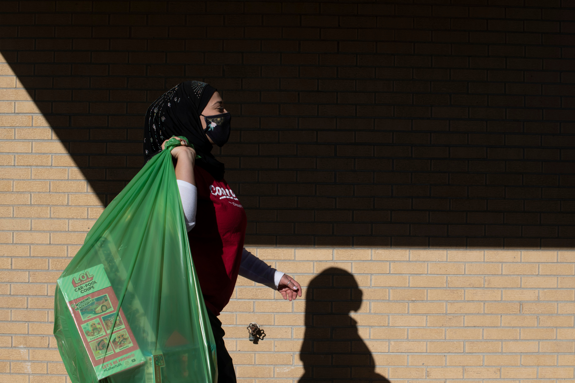Rawan Bardini, a Salvation Army volunteer, carries a bag of toys for a participant during the Salvation Army Angel Tree program's toy giveaway on Tuesday, Dec. 22, 2020 at the Salvation Army in Aurora, Colorado.