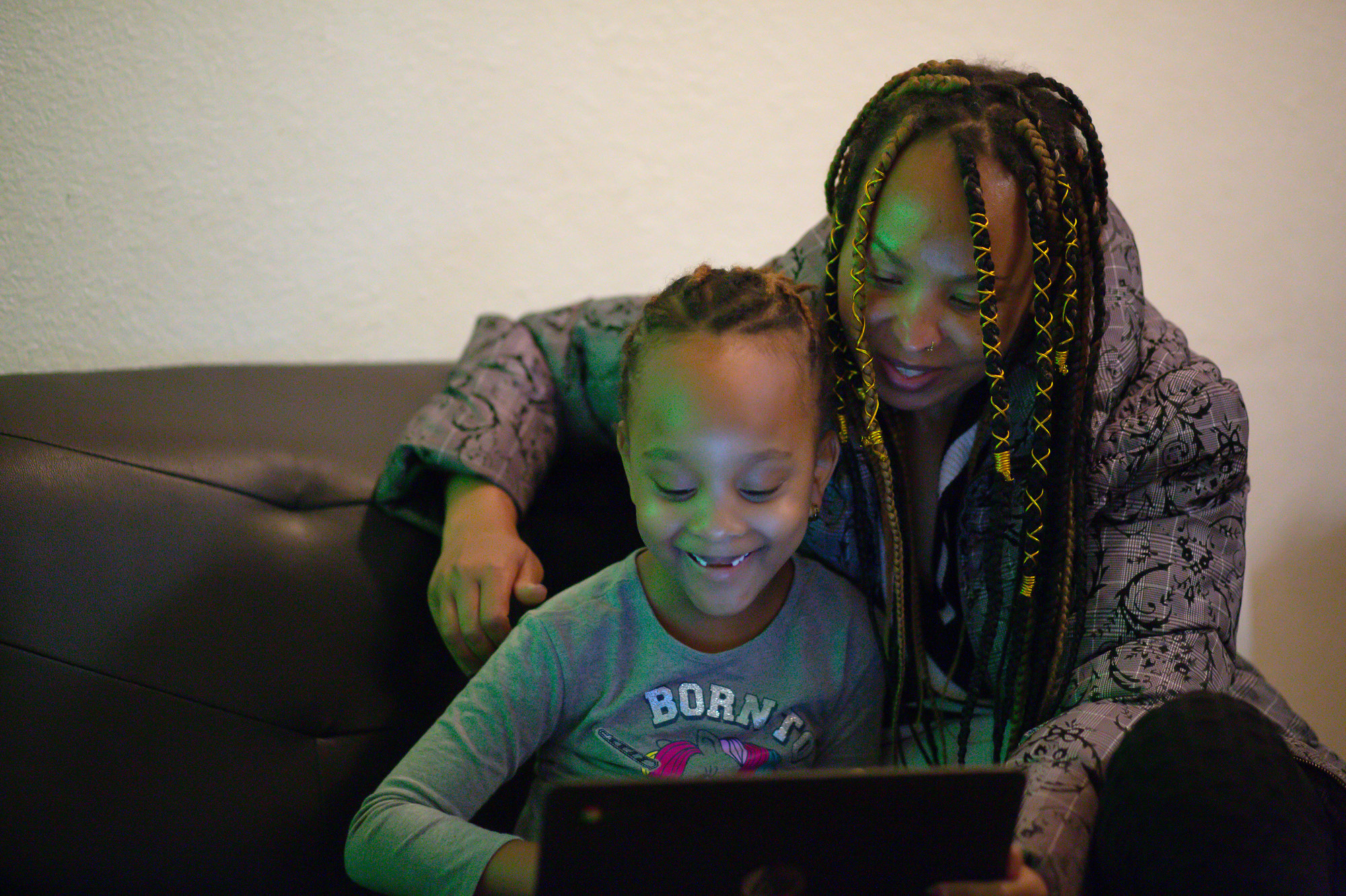 Khan Mwezi helps her daughter, Martinode, with schoolwork at their home in Aurora, Nov. 14, 2020.