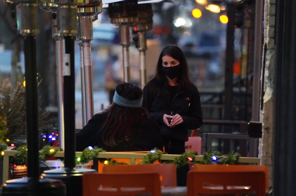 A waitperson wears a face mask.