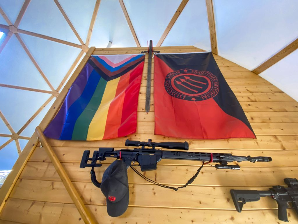 Various assault weapons and flags adorn the wall leading up to the ranch house's second floor on April 27, 2021.