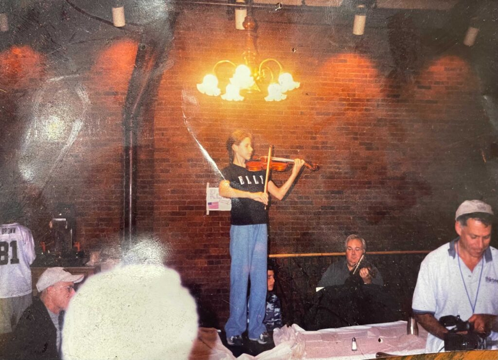 An 11-year-old Magee Capsouto stands on a table while playing the violin in a restaurant.